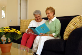 Two senior women looking at a photo album together in living room